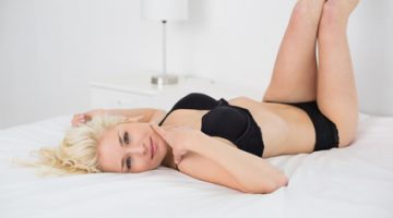 Portrait of a beautiful young woman lying in black lingerie on bed