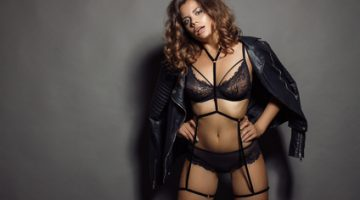Sexy young woman in black underwear and a leather jacket. The girl with a professional make-up and hair styling.