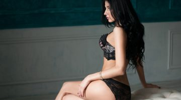 adorable girl in lingerie in boudoir style sit on ottoman in profile